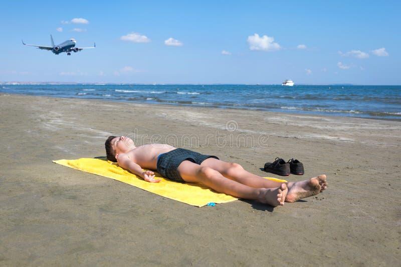 Το αγόρι εφήβων βρίσκεται στην κίτρινη πετσέτα και κάνει ηλιοθεραπεία στην παραλία κάτω από τα προσγειωμένος αεροπλάνα Ταξίδι σε  στοκ φωτογραφίες με δικαίωμα ελεύθερης χρήσης