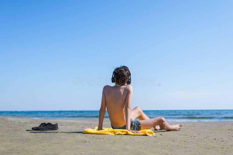Το αγόρι εφήβων κάθεται στην κίτρινη πετσέτα στα ακουστικά και κάνει ηλιοθεραπεία στην παραλία στο υπόβαθρο θάλασσας και ουρανού  στοκ φωτογραφία με δικαίωμα ελεύθερης χρήσης