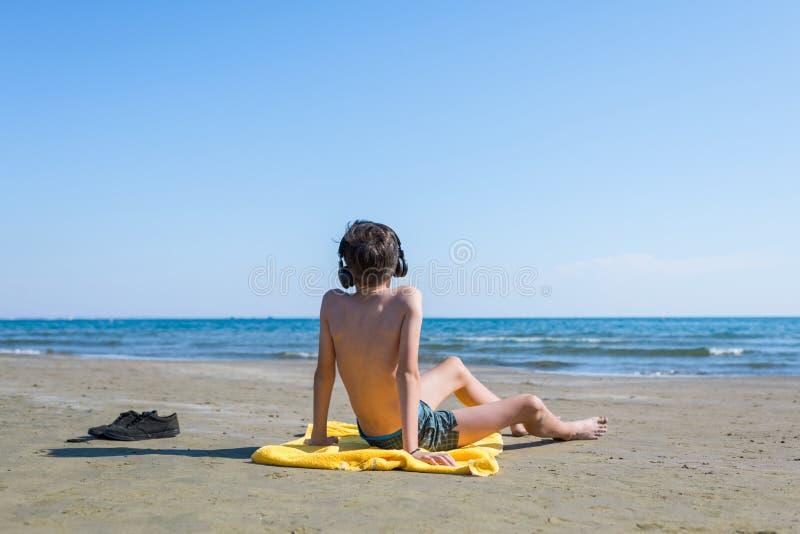 Το αγόρι εφήβων κάθεται στην κίτρινη πετσέτα στα ακουστικά και κάνει ηλιοθεραπεία στην παραλία στο υπόβαθρο θάλασσας και ουρανού  στοκ εικόνες με δικαίωμα ελεύθερης χρήσης