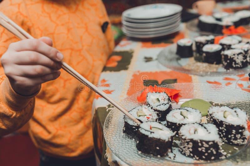 Το αγόρι εφήβων παίρνει το ρόλο σουσιών του πιάτου που τρώει στοκ φωτογραφίες με δικαίωμα ελεύθερης χρήσης