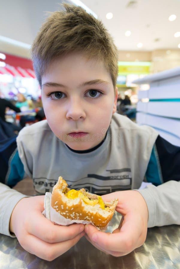 Το αγόρι εφήβων τρώει τον καφέ χάμπουργκερ ν στοκ φωτογραφία
