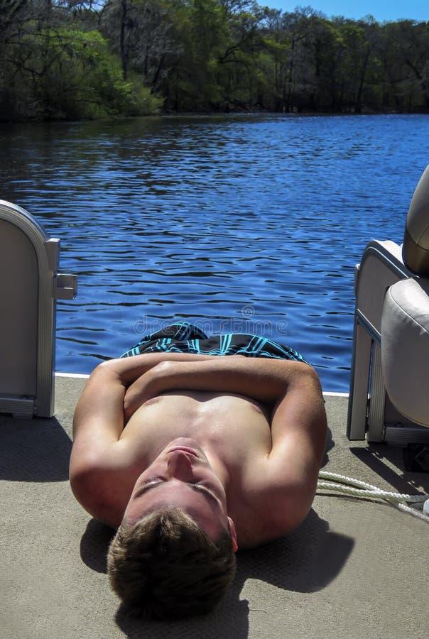 Το αγόρι εφήβων χαλαρώνει στον ήλιο στοκ φωτογραφία με δικαίωμα ελεύθερης χρήσης