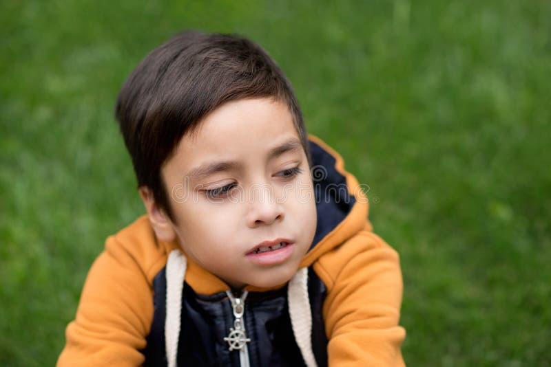 Το αγόρι κάθεται σε έναν χορτοτάπητα και σκέφτεται στοκ εικόνες με δικαίωμα ελεύθερης χρήσης