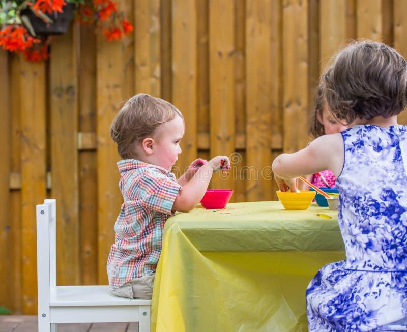 Το αγόρι κάθεται τη βαφή των αυγών Πάσχας μαζί με τα παιδιά στοκ εικόνες