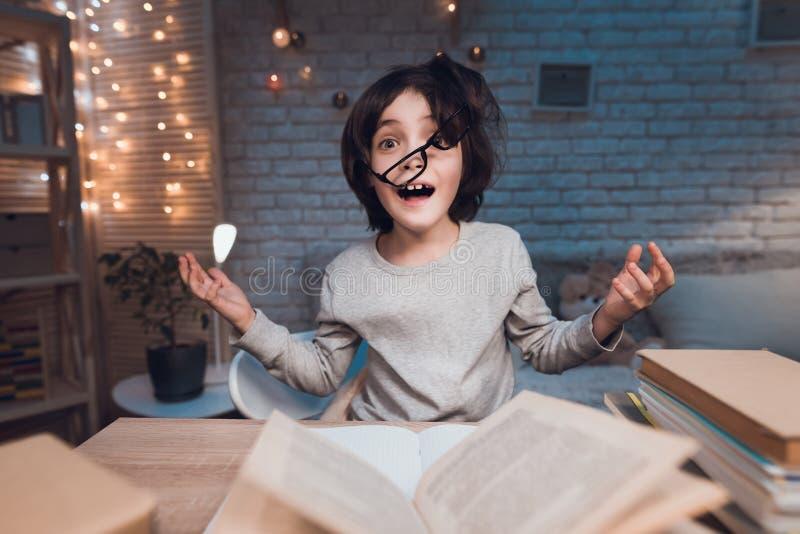 Το αγόρι κάνει την εργασία για το σχολείο που περιβάλλεται από τα βιβλία τη νύχτα στο σπίτι στοκ εικόνες