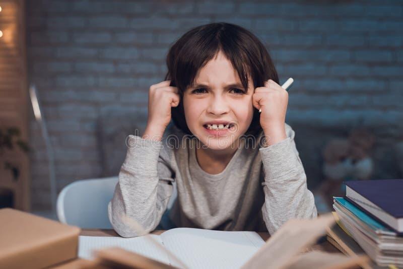Το αγόρι κάνει την εργασία για το σχολείο που περιβάλλεται από τα βιβλία τη νύχτα στο σπίτι στοκ εικόνα