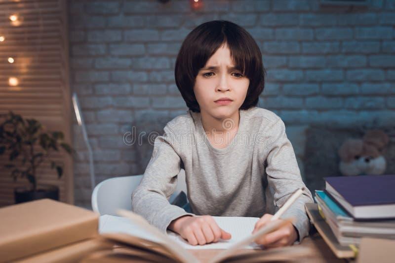 Το αγόρι κάνει την εργασία που περιβάλλεται από τα βιβλία τη νύχτα στο σπίτι στοκ φωτογραφία με δικαίωμα ελεύθερης χρήσης