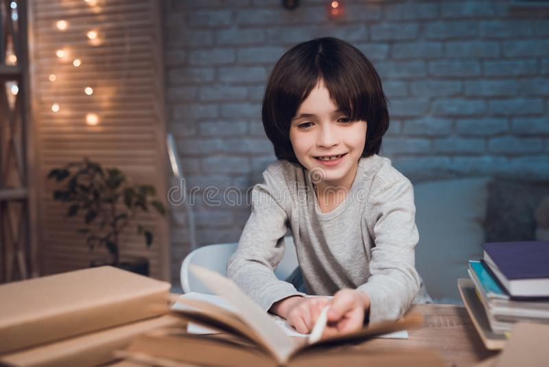 Το αγόρι κάνει την εργασία που περιβάλλεται από τα βιβλία τη νύχτα στο σπίτι στοκ εικόνες