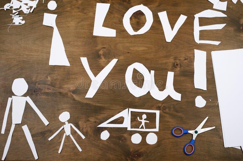 Το αγόρι κάνει το origami - αυτοκίνητο και οικογένεια, παιδιά, γονέας, σ' αγαπώ κείμενο, τοπ άποψη στο ξύλινο υπόβαθρο στοκ φωτογραφία με δικαίωμα ελεύθερης χρήσης