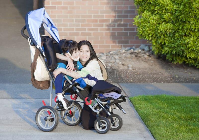 το αγόρι καθιστούσε ανίκανη την αναπηρική καρέκλα αδελφών του στοκ εικόνες