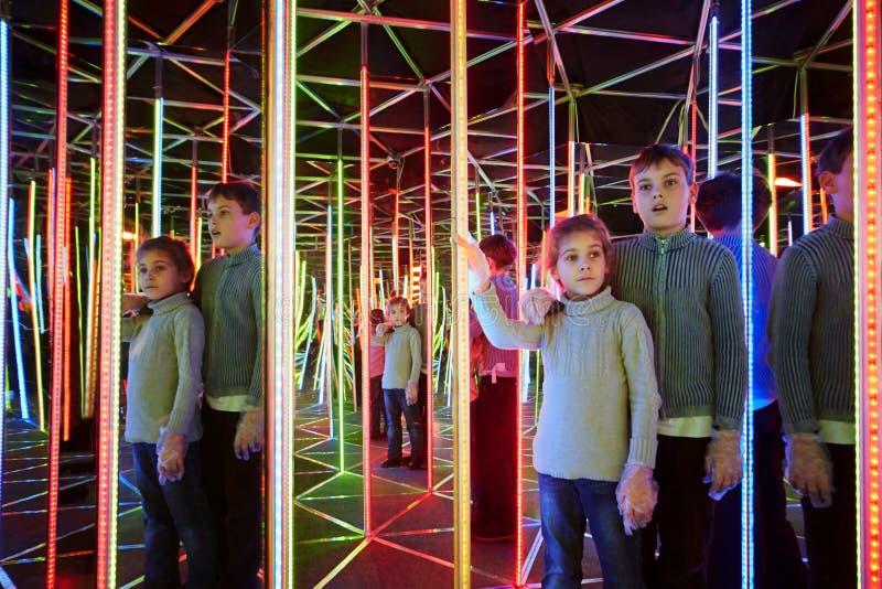 Το αγόρι και η αδελφή περιπλανιούνται στο semidarkness του λαβύρινθου καθρεφτών στοκ εικόνες