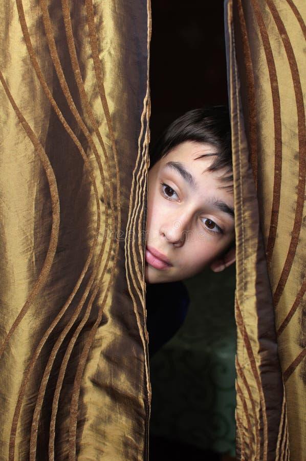 Το αγόρι και η κουρτίνα στοκ εικόνα