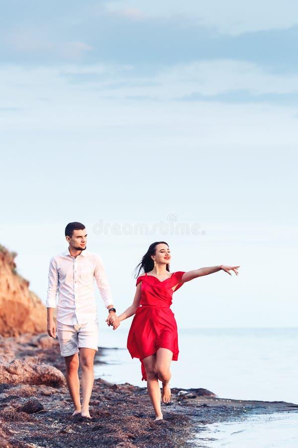 Το αγόρι και το κορίτσι πηγαίνουν κατά μήκος των χεριών εκμετάλλευσης ακτών Η γυναίκα παρουσιάζει δάχτυλο στη θάλασσα στοκ φωτογραφία με δικαίωμα ελεύθερης χρήσης