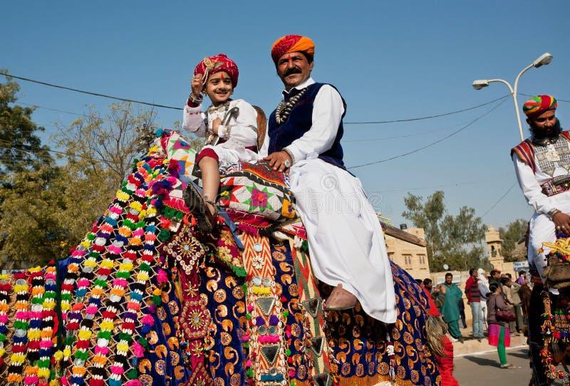 Το αγόρι και ο πατέρας του οδηγούν την καμήλα στοκ φωτογραφίες