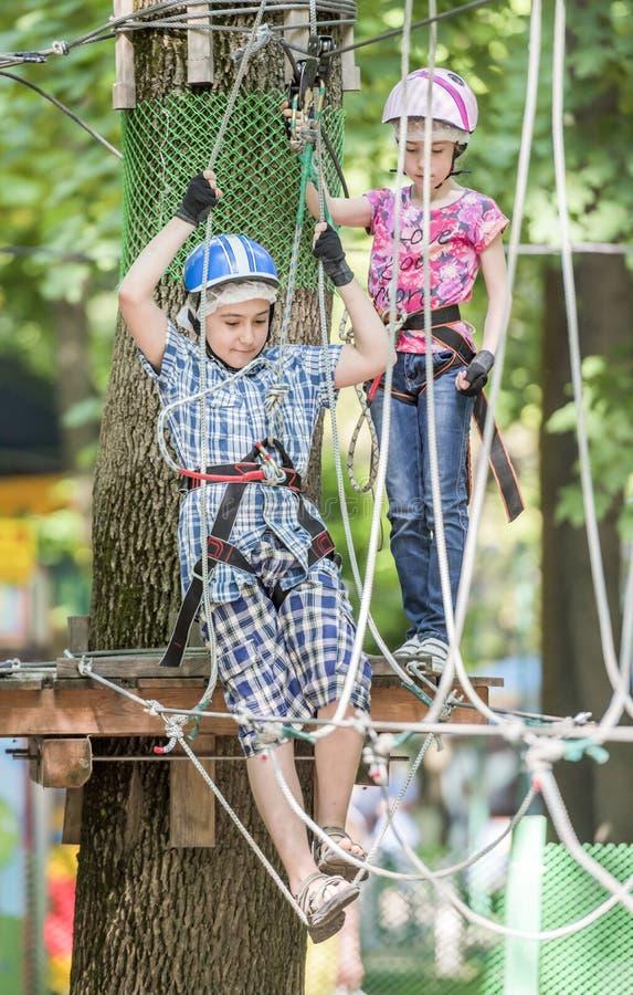 Το αγόρι και το κορίτσι εκπαιδεύονται στο πάρκο σχοινιών στοκ φωτογραφία με δικαίωμα ελεύθερης χρήσης
