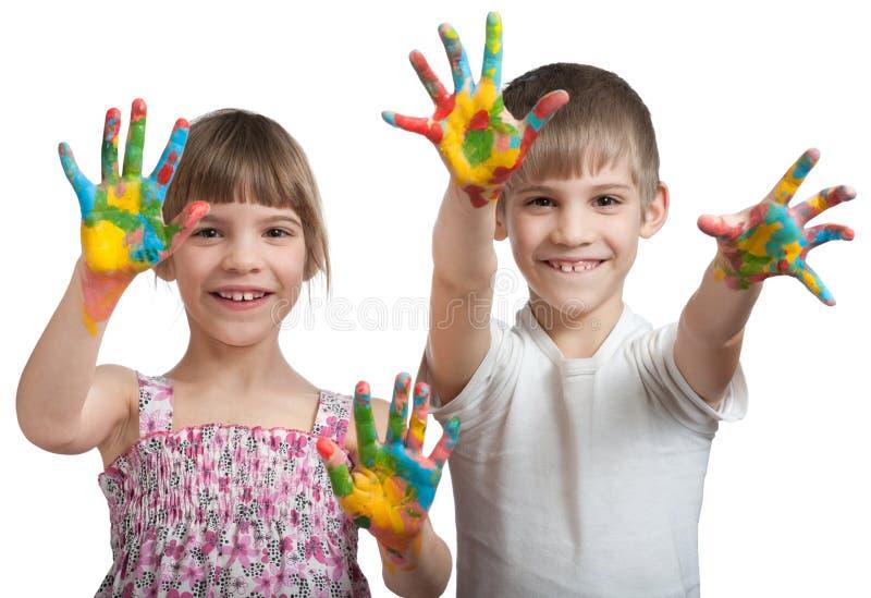 Τα παιδιά εμφανίζουν χέρια τους που λερώνονται σε ένα χρώμα στοκ εικόνα