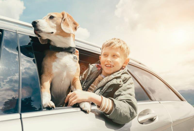 Το αγόρι και το σκυλί κοιτάζουν έξω από το παράθυρο αυτοκινήτων στοκ φωτογραφίες