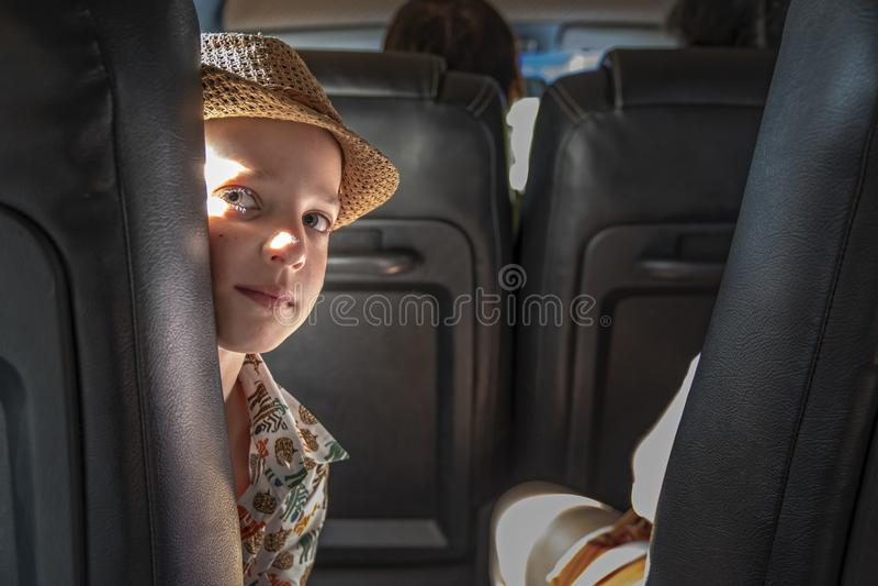 Το αγόρι κοιτάζει έξω από την πίσω καρέκλα στο επιβάτη αεροπλάνου καμπινών Πορτρέτο ενός χαμογελώντας παιδιού 8-10 έτη στο φως απ στοκ φωτογραφία με δικαίωμα ελεύθερης χρήσης