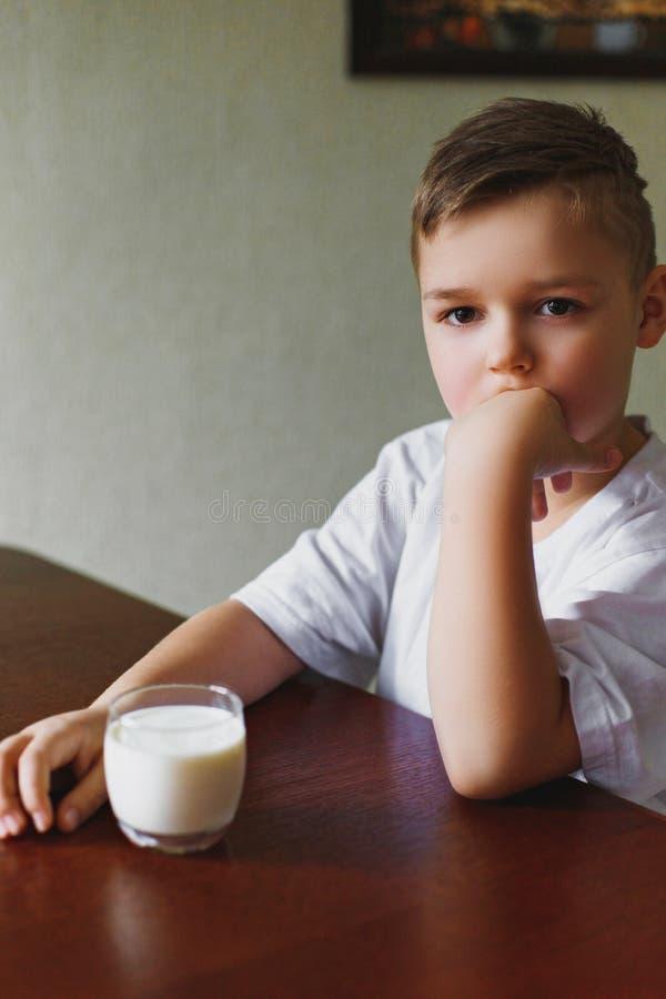 Το αγόρι κοιτάζει δυστυχώς στην απόσταση Ένα ποτήρι του γάλακτος, ένα mornin στοκ εικόνες