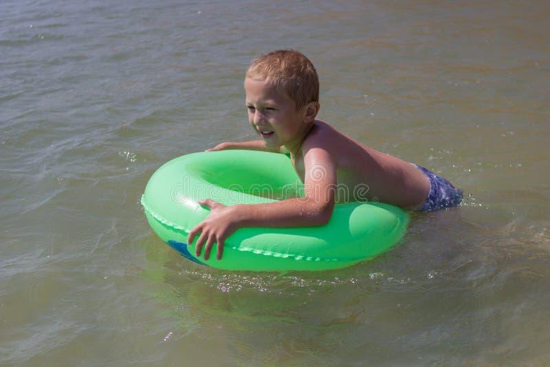 Το αγόρι κολυμπά σε έναν διογκώσιμο κύκλο, ευτυχής απόλαυση αγοριών γέλιου που κολυμπά στη θάλασσα στοκ εικόνα