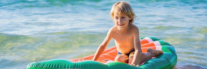 Το αγόρι κολυμπά στη θάλασσα σε ένα διογκώσιμο ΕΜΒΛΗΜΑ στρωμάτων, ΜΑΚΡΟΧΡΟΝΙΟ ΣΧΗΜΑ στοκ φωτογραφία