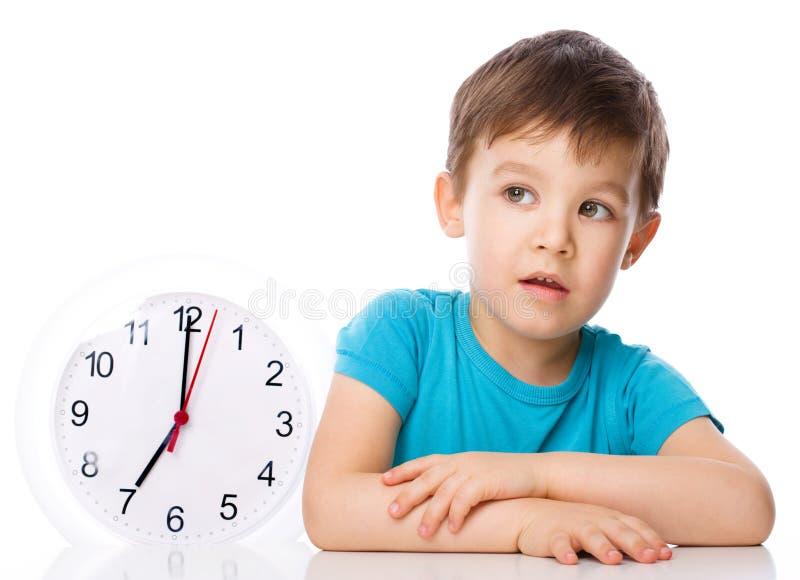 Το αγόρι κρατά το μεγάλο ρολόι στοκ εικόνα με δικαίωμα ελεύθερης χρήσης
