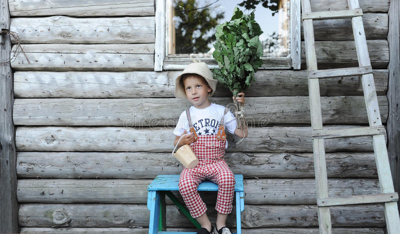 Το αγόρι με μια δρύινη σκούπα Υπόλοιπο στο χωριό Λουτρό, ξύλινο σπίτι στοκ εικόνες