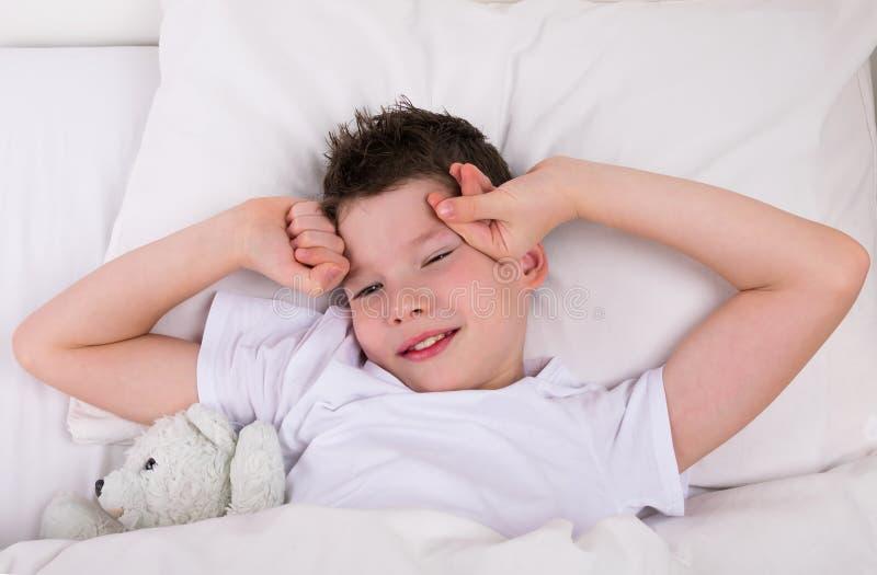 Το αγόρι με μια teddy αρκούδα ξύπνησε στο κρεβάτι στοκ εικόνα με δικαίωμα ελεύθερης χρήσης