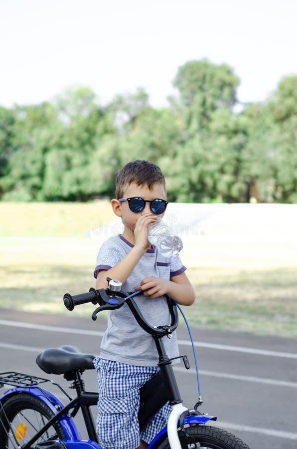 Το αγόρι με το ποδήλατο πίνει το εμφιαλωμένο νερό στοκ εικόνες