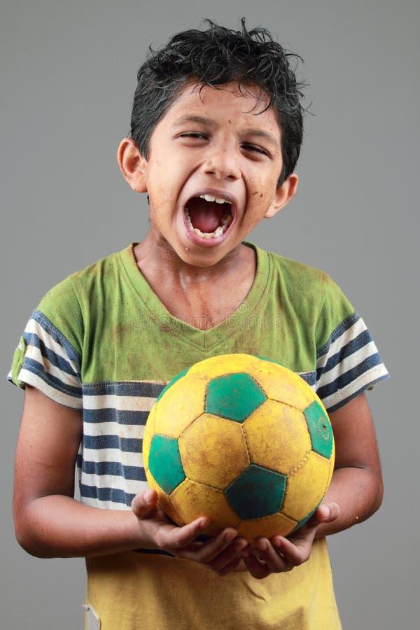Το αγόρι με το σώμα που λερώνεται με τη λάσπη κρατά ένα ποδόσφαιρο και παρουσιάζει έκφραση πόνου στοκ φωτογραφίες