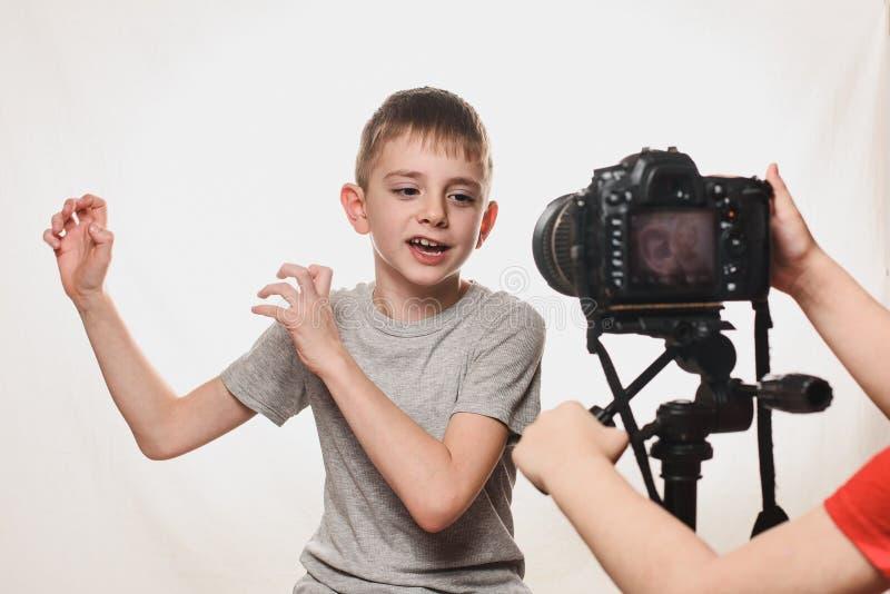 Το αγόρι μιλάει με ενθουσιασμό στην κάμερα Χέρια παιδιών με κάμερα στο πλαίσιο Νέος blogger με βίντεο Λευκό φόντο στοκ φωτογραφία