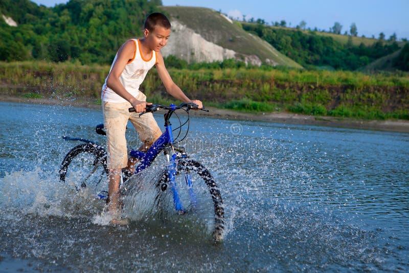 το αγόρι οδηγά το ποδήλατό του κατά μήκος του ποταμού στοκ εικόνες με δικαίωμα ελεύθερης χρήσης