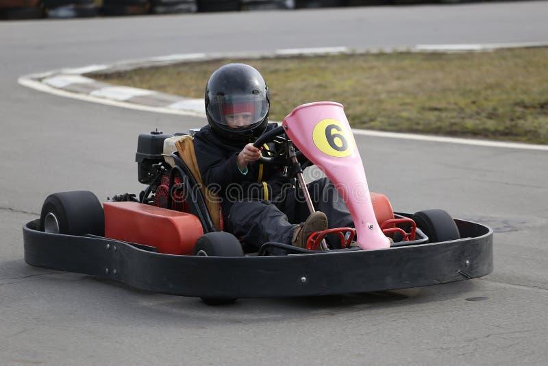 Το αγόρι οδηγεί πηγαίνει -πηγαίνω-kart αυτοκίνητο με την ταχύτητα σε μια διαδρομή αγώνα παιδικών χαρών στοκ φωτογραφία