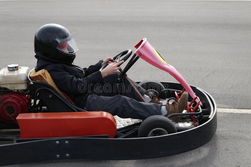 Το αγόρι οδηγεί πηγαίνει -πηγαίνω-kart αυτοκίνητο με την ταχύτητα σε μια διαδρομή αγώνα παιδικών χαρών στοκ φωτογραφία με δικαίωμα ελεύθερης χρήσης