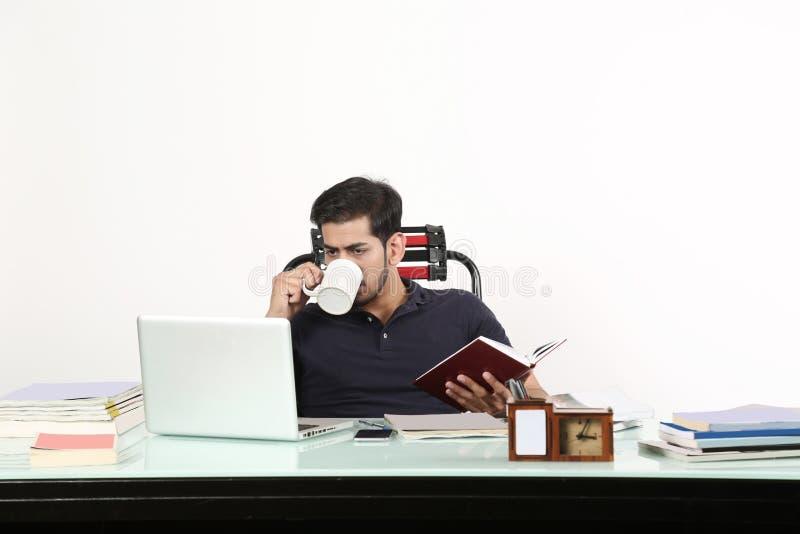 Το αγόρι πίνει τον καφέ και κοιτάζει στο lap-top στοκ εικόνες