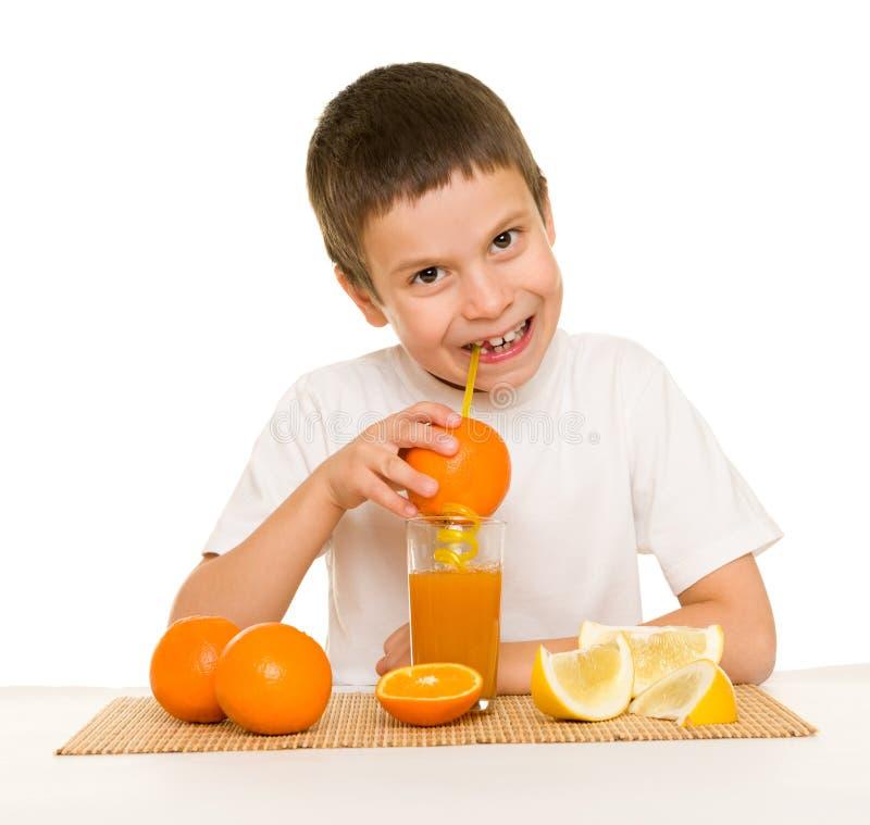 Το αγόρι πίνει το χυμό από πορτοκάλι με ένα άχυρο στοκ φωτογραφίες με δικαίωμα ελεύθερης χρήσης