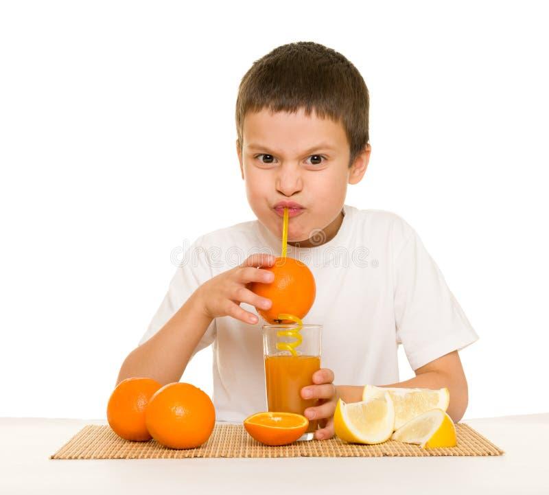 Το αγόρι πίνει το χυμό από πορτοκάλι με ένα άχυρο στοκ φωτογραφία με δικαίωμα ελεύθερης χρήσης
