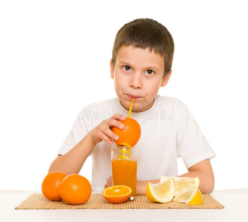 Το αγόρι πίνει το χυμό από πορτοκάλι με το άχυρο στοκ φωτογραφίες