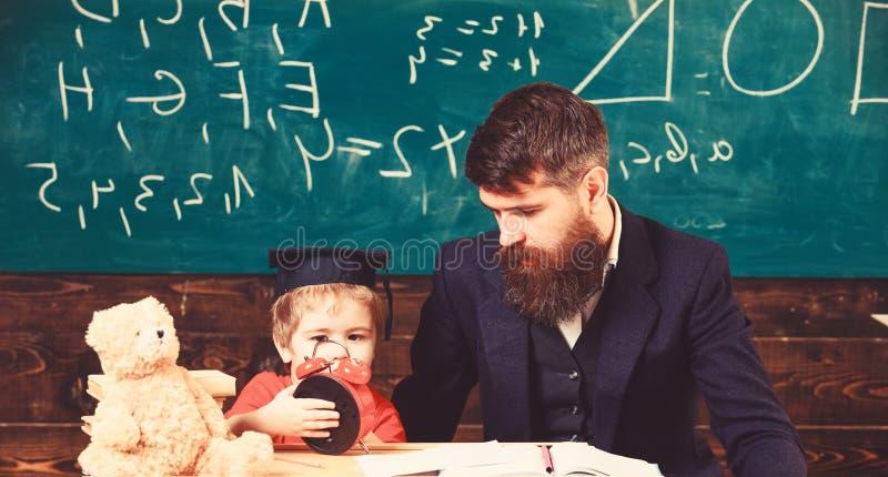 Το αγόρι, παιδί στο ήρεμο πρόσωπο κρατά το ξυπνητήρι ενώ συζήτηση δασκάλων στο παιδί Ο δάσκαλος με τη γενειάδα, πατέρας διδάσκει  στοκ εικόνες