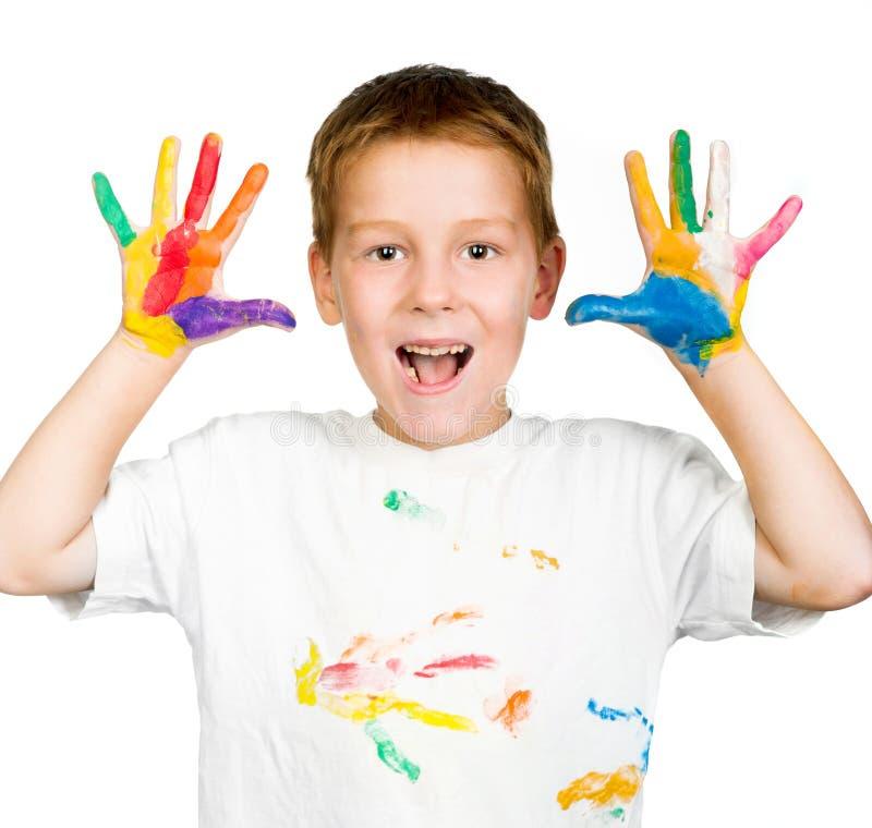 Το αγόρι παρουσιάζει χέρια του που χρωματίζονται με το χρώμα στοκ εικόνες