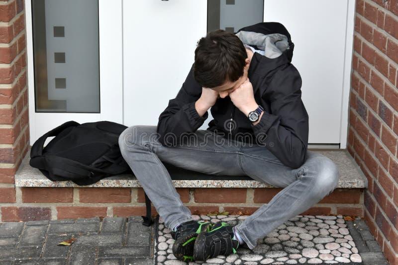 Το αγόρι περιμένει κάποιο με το κλειδί μπροστινών πορτών στοκ εικόνα