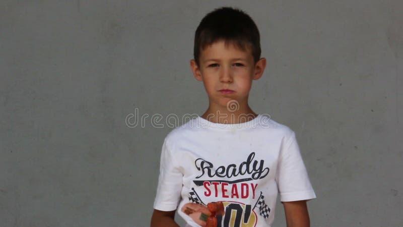 Το αγόρι που τρώει ένα λουκάνικο σε ένα γκρίζο αγόρι υποβάθρου επεκτείνεται και λουκάνικων δαγκώματα απόθεμα βίντεο