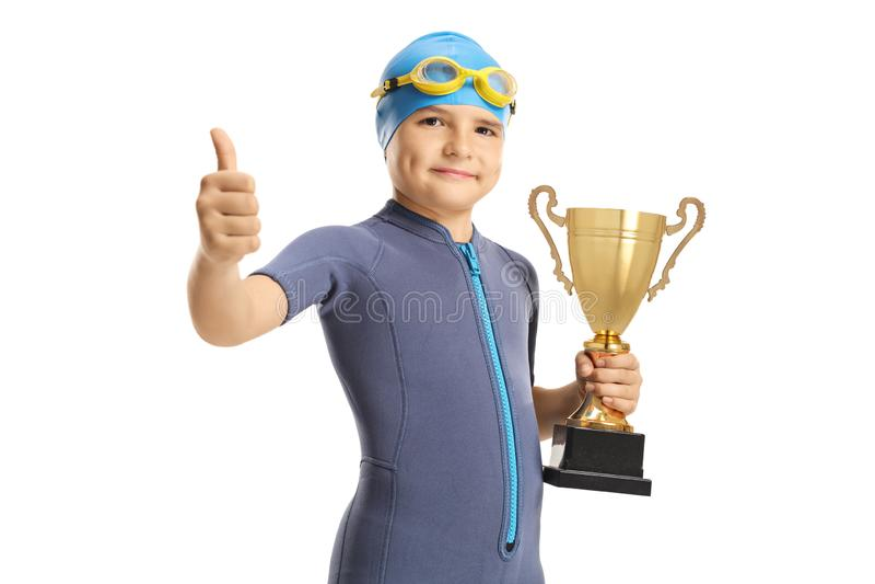 Το αγόρι που φορά ένα wetsuit και μια κολύμβηση ΚΑΠ και googles και το κράτημα μιας χρυσής παρουσίασης τροπαίων φυλλομετρεί επάνω στοκ εικόνες