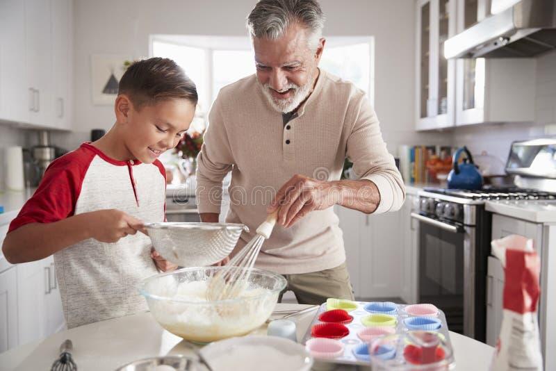 Το αγόρι προ-εφήβων που κάνει το μίγμα κέικ στην κουζίνα με τον παππού του, κλείνει επάνω στοκ εικόνες