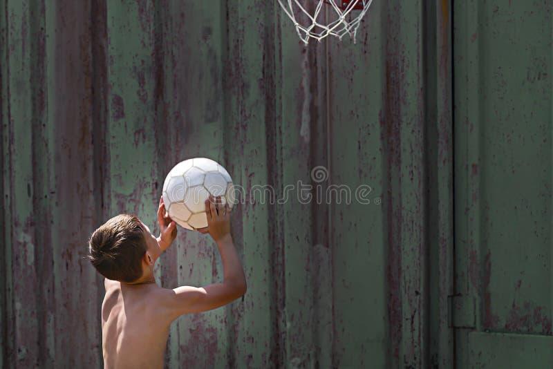 Το αγόρι ρίχνει τη σφαίρα στο δαχτυλίδι στοκ εικόνες