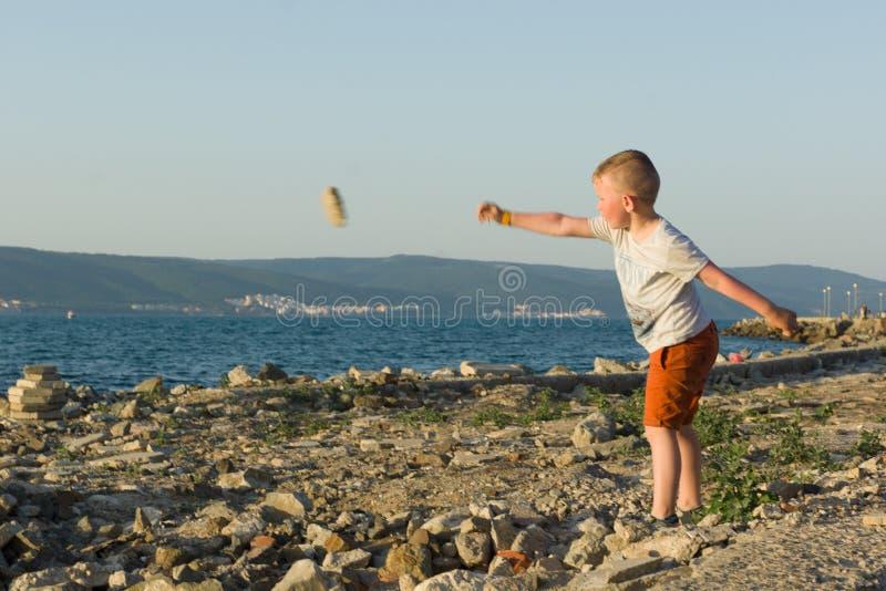 Το αγόρι ρίχνει τις πέτρες εν πλω στοκ εικόνες