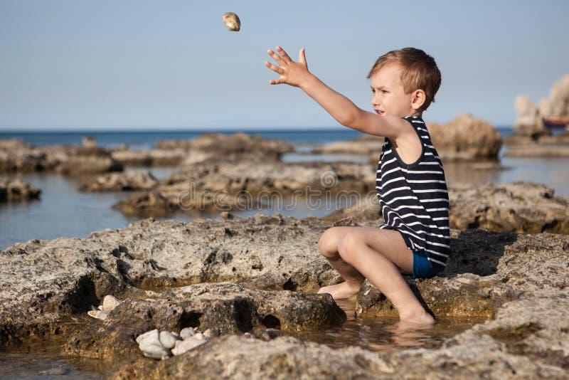 Το αγόρι ρίχνει τις πέτρες στη θάλασσα στοκ εικόνες