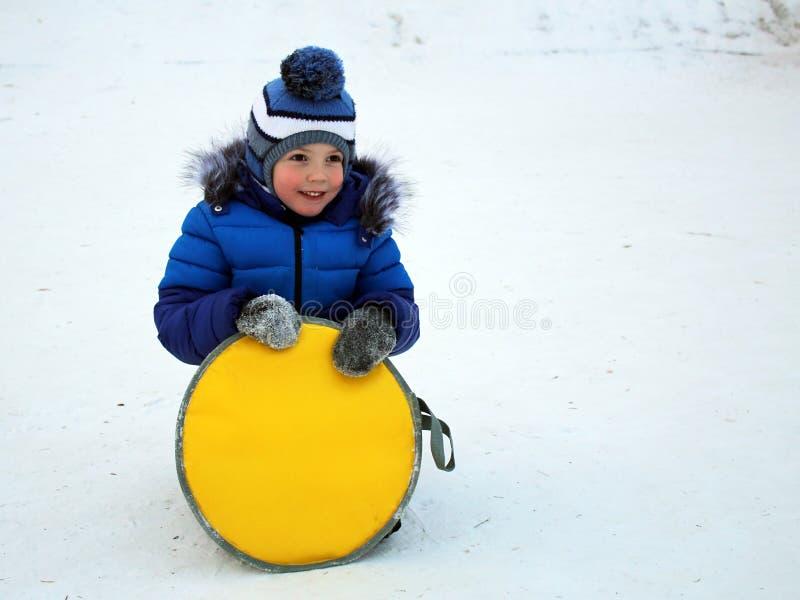 Το αγόρι σε ένα θερμό μπλε καπέλο περπατά έξω το χειμώνα στοκ εικόνα