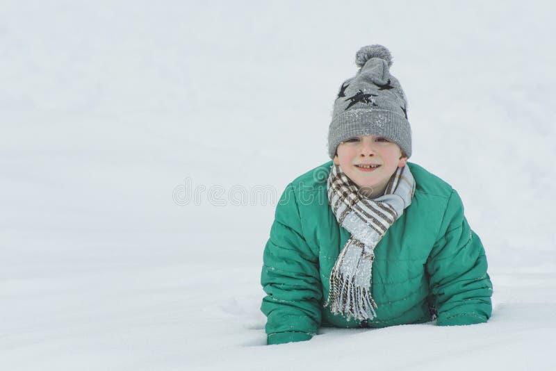Το αγόρι σε ένα καπέλο, ένα μαντίλι και ένα πράσινο σακάκι βρίσκεται στο χιόνι στους αγκώνες του Πορτρέτο Κινηματογράφηση σε πρώτ στοκ φωτογραφίες