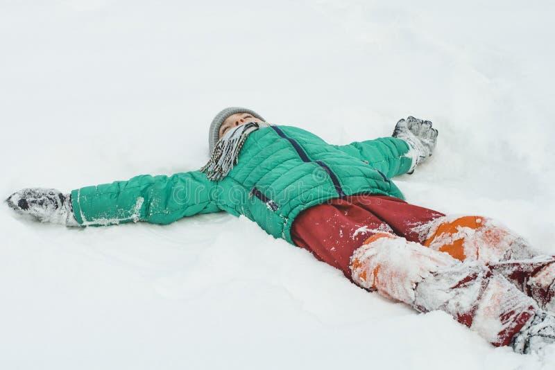 Το αγόρι σε ένα πράσινο σακάκι και κόκκινα εσώρουχα που βρίσκονται στην πλάτη του στο χιόνι με τα όπλα ο μπλε παγετός σκοτεινής μ στοκ φωτογραφίες με δικαίωμα ελεύθερης χρήσης